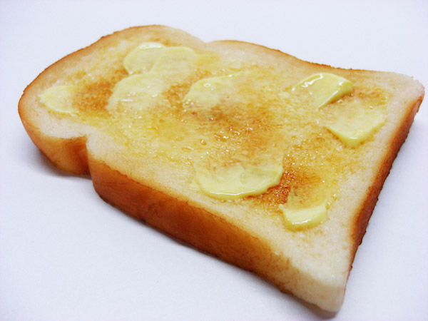 A slice of toast with butter on it.