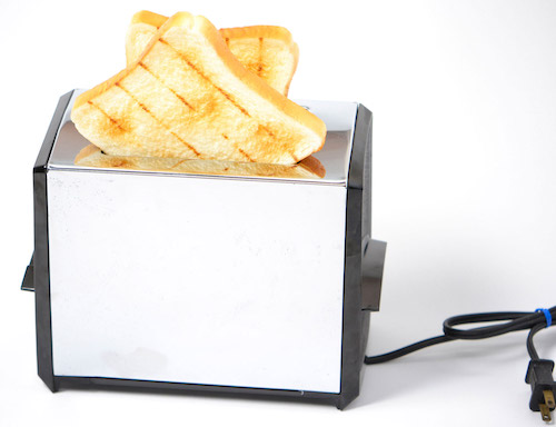 A toaster with slices of bread at the top.